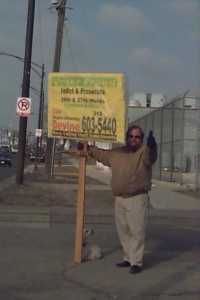 Wayne Strnad holding picket sign telling people to call Devine